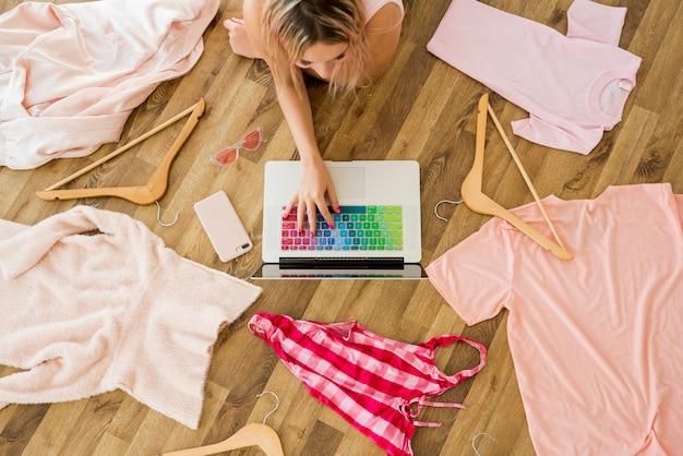 Bovenaanzicht laptop omringd door kleding