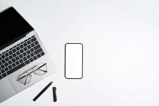 Bovenaanzicht laptopcomputer, bril en smartphone op witte tafel.