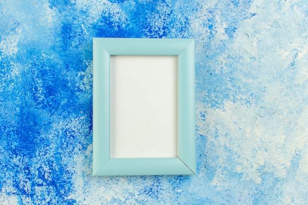 Bovenaanzicht leeg fotolijstje op blauwe abstract
