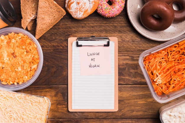 Bovenaanzicht leeg klembord en lunch op het werk post-it met eten