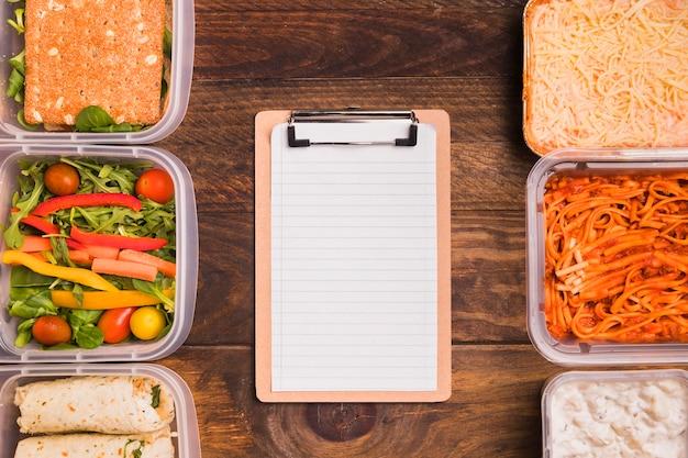 Bovenaanzicht leeg klembord met lunchboxen