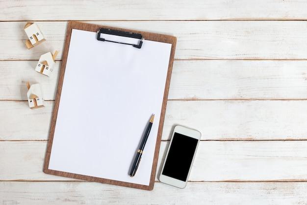 Bovenaanzicht, leeg klembord met miniatuur witte huis en houten smartphone