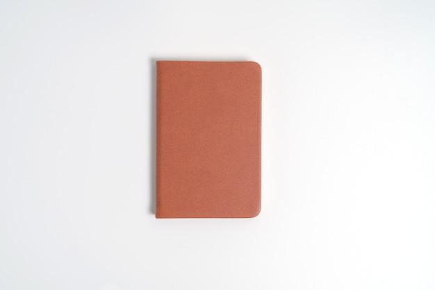 Bovenaanzicht leeg oranje lederen dagboek op wit bureau