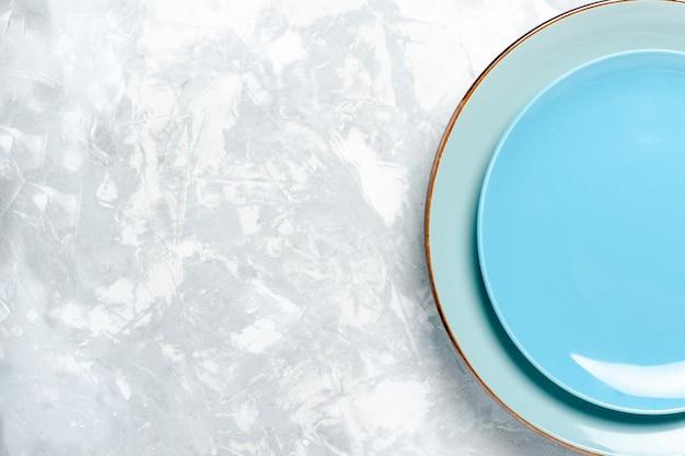 Bovenaanzicht leeg rond bord blauw ed op licht wit vloerbord keuken bestek glas