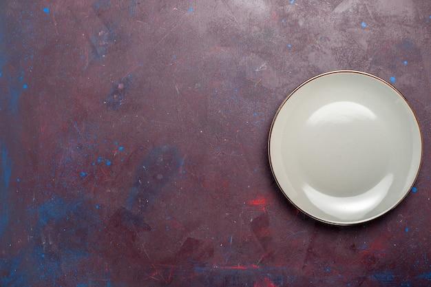 Bovenaanzicht leeg rond glas gemaakt van grijze plaat op het donkere oppervlak