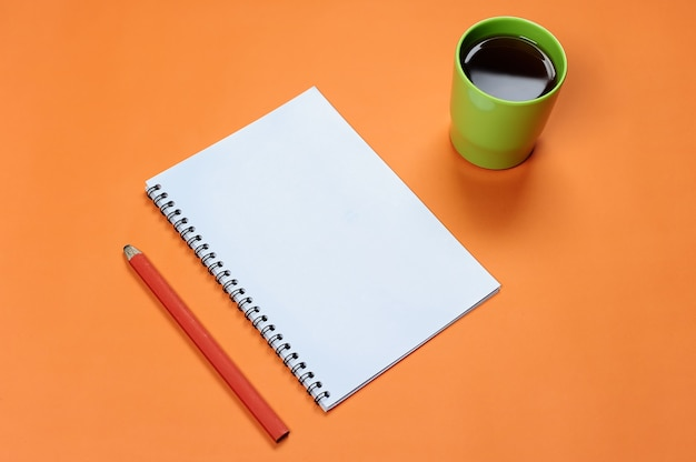 Bovenaanzicht leeg spiraalvormig notitieboekje met potlood en koffiekopje op oranje pastelachtergrond. blanco schrijfblok voor ideeën en inspiratie op gekleurde achtergrond