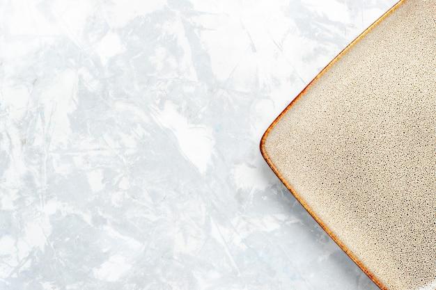 Bovenaanzicht leeg vierkant bord bruin ed op licht wit bureau