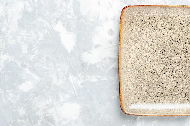 Bovenaanzicht leeg vierkant bord bruin ed op licht wit oppervlak