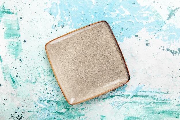 Bovenaanzicht lege bruine plaat vierkant gevormd op blauwe achtergrond keuken eten bord bestek