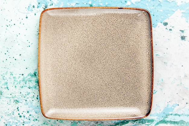 Bovenaanzicht lege bruine plaat vierkant gevormd op lichtblauwe achtergrond keuken eten bord bestek