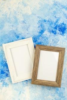 Bovenaanzicht lege fotolijsten op blauw wit