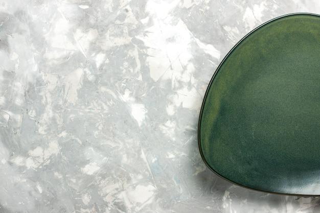 Bovenaanzicht lege groene plaat geïsoleerd op lichtgrijs bureau.