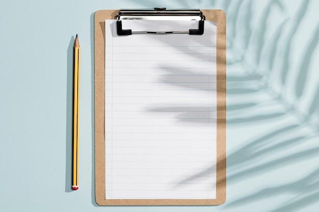 Bovenaanzicht lege klembord papieren en pen met schaduwen