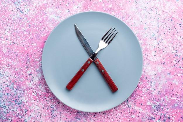 Bovenaanzicht lege plaat blauw gekleurd met vork en mes op roze muur kleur foto plaat eten bestek