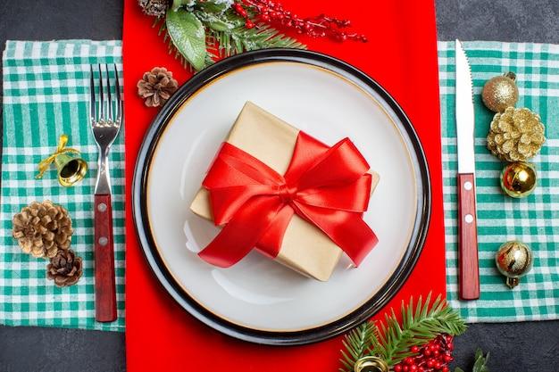 Bovenaanzicht lege plaat met cadeau en kerstspeelgoed en vork op donkere achtergrond