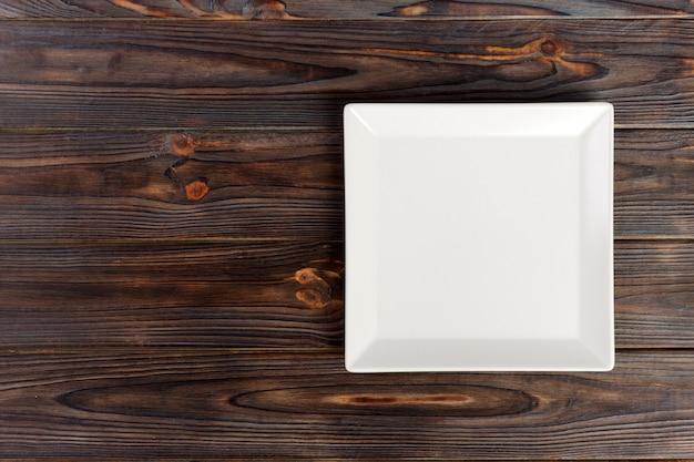 Bovenaanzicht lege plaat op rustieke houten tafel met kopie ruimte