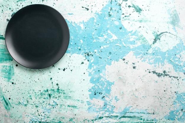 Bovenaanzicht lege ronde plaat donker gekleurd op blauw bureau kleur plaat keuken bestek glas