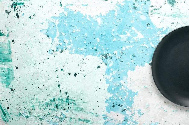 Bovenaanzicht lege ronde plaat donker gekleurd op blauwe achtergrond kleur plaat keuken bestek glazen