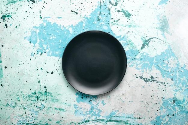 Bovenaanzicht lege ronde plaat donker gekleurd op de blauwe achtergrond kleur plaat keuken bestek glas