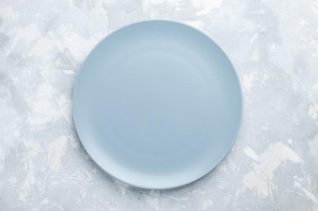 Bovenaanzicht lege ronde plaat ijsblauw gekleurd op het witte bureau bord bestek keuken eten