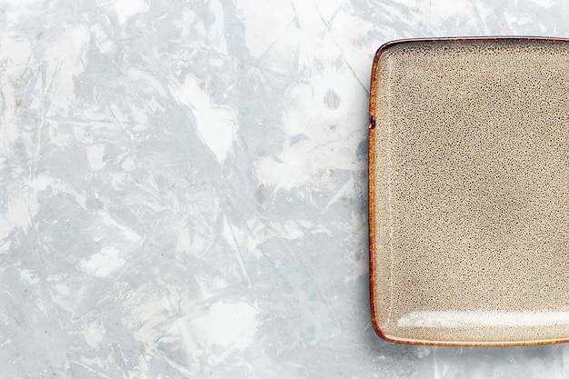 Bovenaanzicht lege vierkante plaat bruin ed op wit oppervlak