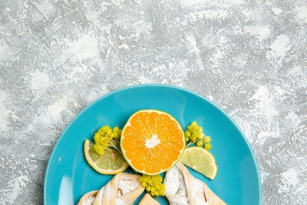 Bovenaanzicht lekker deeg gebak met schijfjes citroen op witte ondergrond