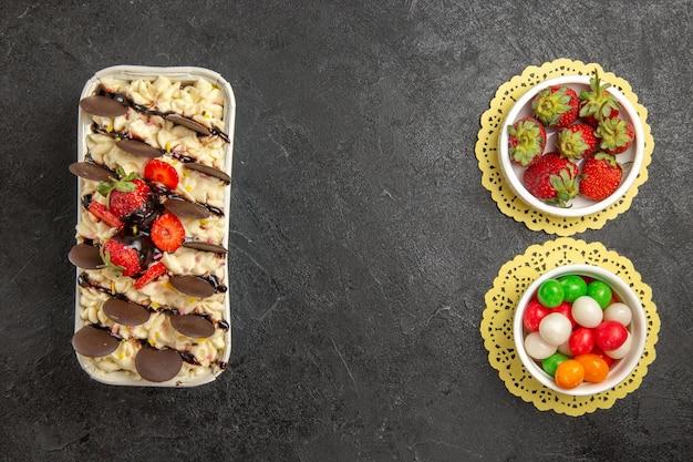 Bovenaanzicht lekker dessert met koekjes en aardbeien op donkergrijze notenkoekje als achtergrond, zoete vruchten, koekjessuiker