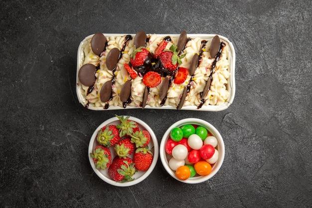 Bovenaanzicht lekker dessert met koekjes en snoepjes op de donkere achtergrond, notenkoekje, zoete fruitkoekjessuiker