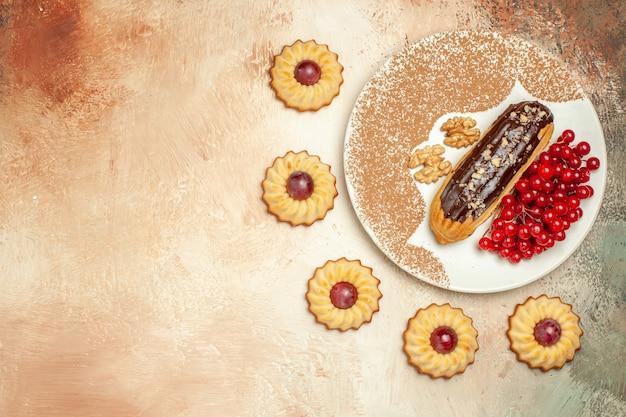 Bovenaanzicht lekker eclair met rode bessen en koekjes op het zoete dessert van de lichte tafelcake