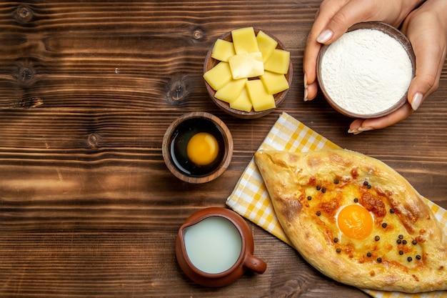Bovenaanzicht lekker eierbrood vers uit de oven met melk op houten bureau deeg bakken brood broodje ei