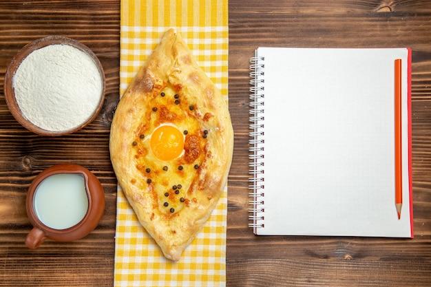 Bovenaanzicht lekker eierbrood vers uit de oven met melk op houten bureau deeg bakken brood broodje eieren