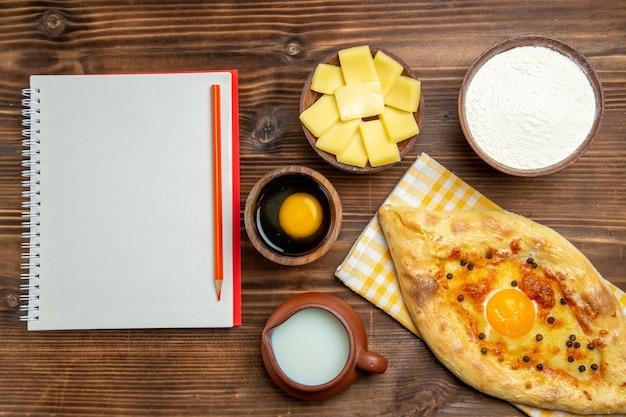 Bovenaanzicht lekker eierbrood vers uit de oven met melk op houten vloer deeg bak brood broodje ei