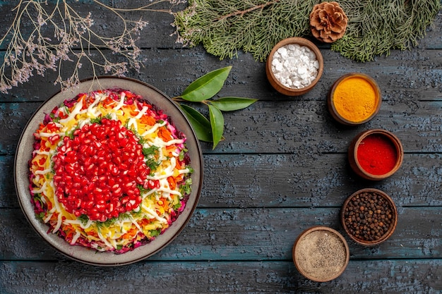 Bovenaanzicht lekker eten lekker kersteten aan de linkerkant en vijf kommen met kleurrijke kruiden aan de rechterkant naast de sparren takken met kegels