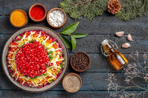 Bovenaanzicht lekker eten smakelijk kerstvoedsel en vijf kommen kleurrijke kruiden naast de fles olie knoflook vuren takken met kegels