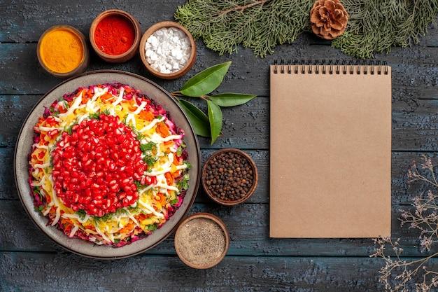 Bovenaanzicht lekker eten, smakelijk kerstvoedsel en vijf kommen met kleurrijke kruiden naast de crèmekleurige sparren takken met kegels