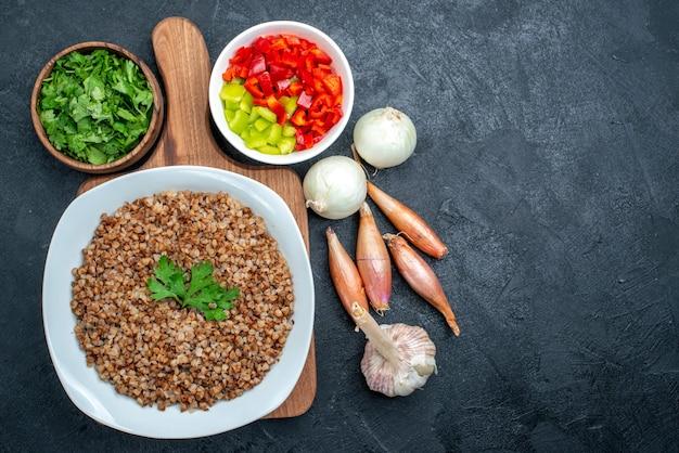 Bovenaanzicht lekker gekookt boekweit met groenen en groenten op de grijze
