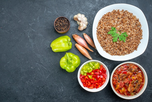Bovenaanzicht lekker gekookt boekweit met groenten op het donkergrijs
