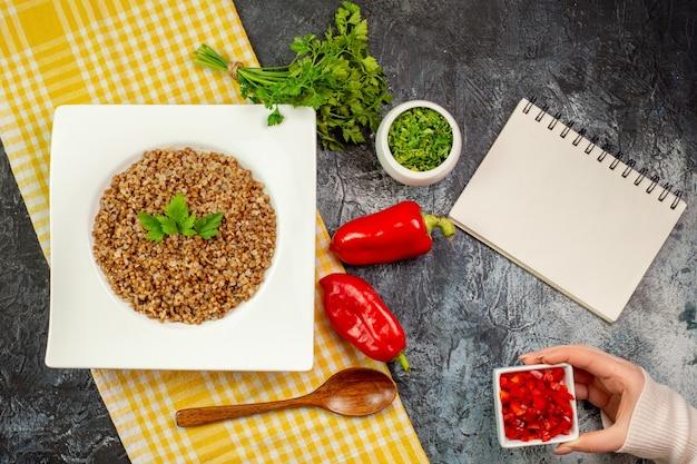 Bovenaanzicht lekker gekookt boekweit met groentjes en paprika op de lichtgrijze tafel