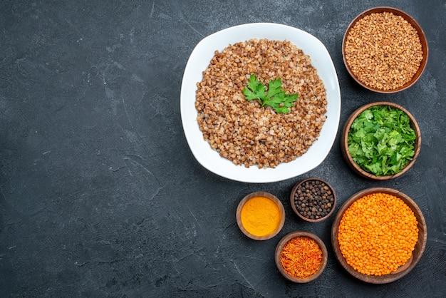 Bovenaanzicht lekker gekookt boekweit met kruiden en groenten op grijs