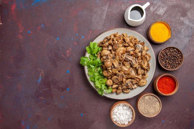 Bovenaanzicht lekker gekookte champignons met greens en kruiden op donker