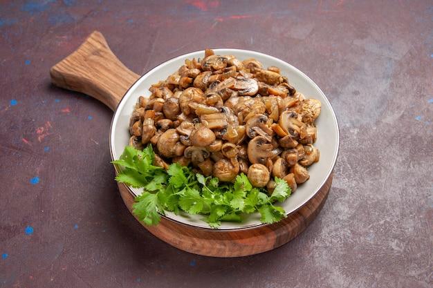 Bovenaanzicht lekker gekookte champignons met greens in het donker
