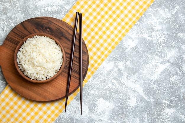 Bovenaanzicht lekker gekookte rijst in bruine plaat op wit