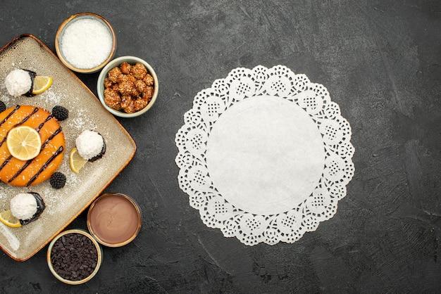 Bovenaanzicht lekker klein taartje met kokossnoepjes op donkergrijs oppervlak cake thee biscuit koekje zoet