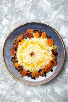 Bovenaanzicht lekker shakh plov gekookte rijstschotel met rozijnen in plaat op wit
