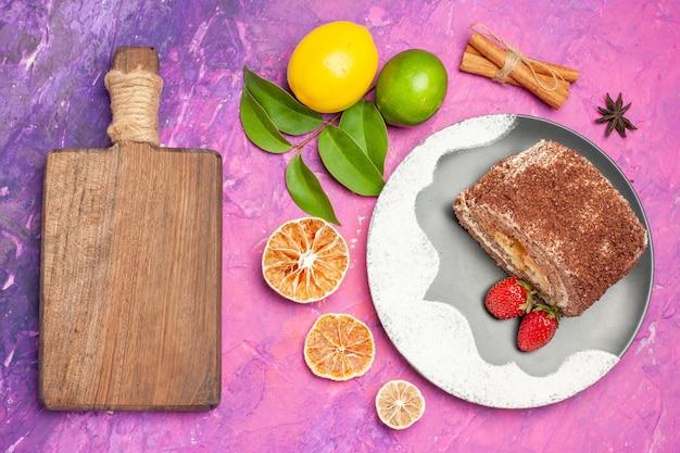 Bovenaanzicht lekker zoet broodje met citroenen op roze achtergrond Gratis Foto