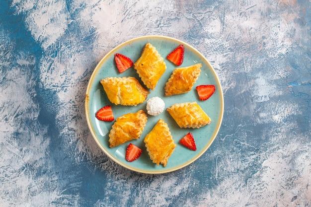 Bovenaanzicht lekker zoet gebak met aardbeien op blauwe achtergrond