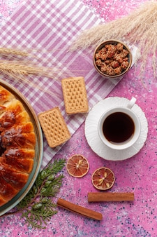 Bovenaanzicht lekkere aardbeientaart fruitige cake met kopje thee op de roze
