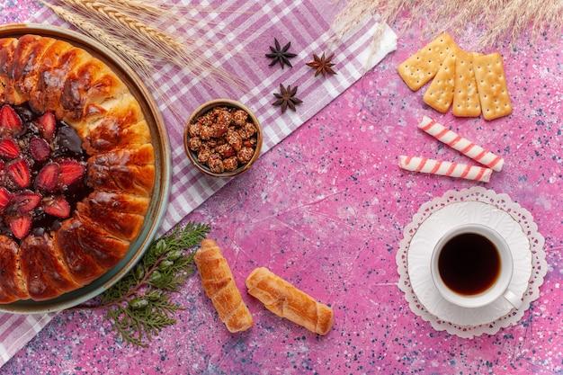 Bovenaanzicht lekkere aardbeientaart fruitige cake met thee op roze
