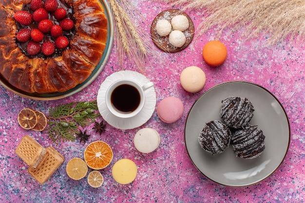 Bovenaanzicht lekkere aardbeientaart met franse macarons en cakes op roze