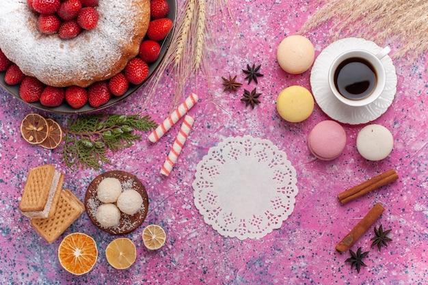 Bovenaanzicht lekkere aardbeientaart met franse macarons en kopje thee op roze
